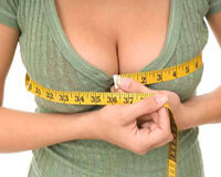Picture of a woman measuring her reduced breasts