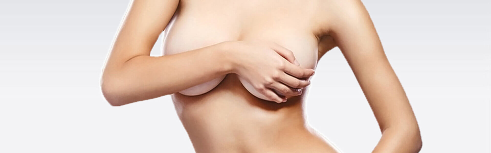 Picture a woman with a hand over a breast depicting plastic surgery in San José, Costa Rica.
